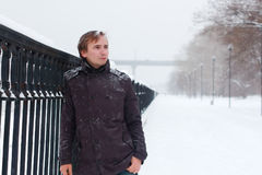 Young man with snowflakes in hair stands near fence. Young man with snowflakes in hair stands near metal black fence at winter snowy day Stock Photography