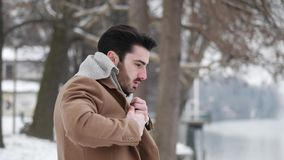 Young man in snowy city putting on gloves. Handsome young man standing outside in winter, in snowy Turin, in Italy, on river docks, putting on wool scarf stock video footage