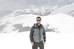 Young man and snowy mountains in the background Stock Photography