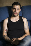 Young man in sofa with cool tattoos Stock Photography