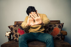 Young man on sofa covering his face Stock Photos