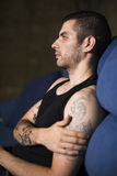 Young man in sofa profile Stock Images
