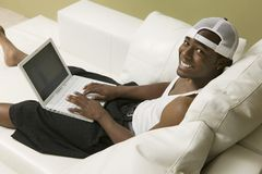 Young man on sofa using laptop high angle view portrait Royalty Free Stock Photography