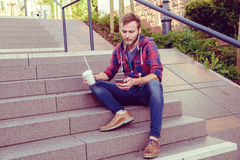 Young man with soft drink sitting on stairs and using his phone Royalty Free Stock Images
