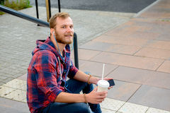 Young man with soft drink sitting on stairs and using his phone Stock Photo