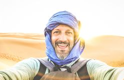 Young man solo traveler taking selfie at Erg Chebbi desert dune. Near Merzouga in Morocco - Adventure wanderlust concept on world famous nature wonder in Maroc royalty free stock photo