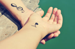 A young man with some musical symbols tattooed in his wrists Royalty Free Stock Photography