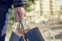 Young man with some shopping bags on the street. Closeup of a young caucasian man seen from behind carrying some paper shopping bags with his purchases on the stock photo