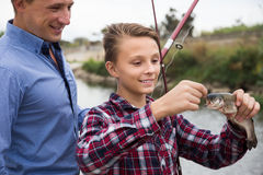 Young man with son looking at fish on hook Royalty Free Stock Photo