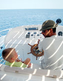 Young man and son on sailboat Royalty Free Stock Images