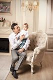 Young man with son sitting in living room Stock Photo