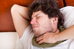 Young man with sore throat. Lying in his bed Stock Photography