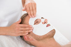 Young Man In Spa Salon With Facial Mask. High Angle View Of Young Man In Spa Salon With Facial Mask stock image
