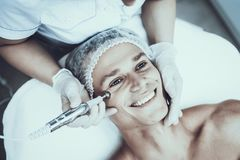 Young Man in Spa Salon for Laser Hair Removal. Guy in Beauty Salon. Modern Cosmetology. Proffesional Cosmetologist. Doctor with Laser Epilator. Men`s Beauty royalty free stock photos