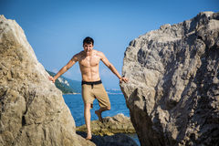 Young Man Spanning Gap Between Coastal Boulders Stock Image