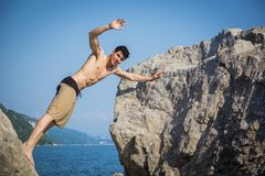 Young Man Spanning Gap Between Coastal Boulders Royalty Free Stock Images