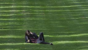Young Man Speaking On Cell Phone In The Park. Young Adult Male Casually Dressed Laying On The Grass With His Cell Phone Talking, Enjoying A Sunny Early Autumn stock footage
