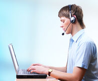 Young man speaking by hands-free and typing Stock Image