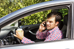 Young man speaking on phone and drinking coffee while driving Royalty Free Stock Photo