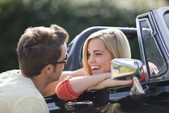 A young man speaking to a young woman in a black sports car Royalty Free Stock Photos