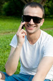Young man speaks on the phone on the grass Royalty Free Stock Image
