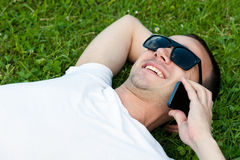 Young man speaks on the phone lying on the grass Royalty Free Stock Images