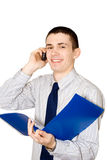 The young man speaks to phone. The young man holds in a hand a blue folder with documents and speaks by mobile phone Royalty Free Stock Image
