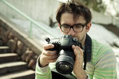 Young man in spectacles with camera Royalty Free Stock Images