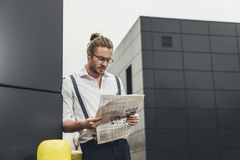 Young man in spectacles leaning at modern building wall and reading newspaper Stock Images