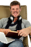 Young man with spectacles, relaxing time. Young attractive caucasian man headset and netbook, wearing spectacles, lying on sofa and reading book. Relaxing time Royalty Free Stock Photos