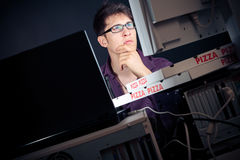 Young Man Spending His Night With Computers. Nerd sitting in front of his computers all night long stock photography