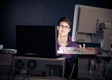 Young Man Spending His Night With Computers. Nerd sitting in front of his computers all night long royalty free stock photography