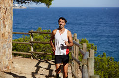 The young man spends time outdoors jogging on zhipopisnoy hilly terrain near the ocean Stock Image