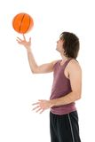 Young man with spinning basketball at his forefinger. Isolated on white Royalty Free Stock Images