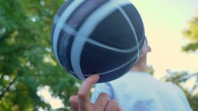 Young man spinning basketball on one finger in park, outdoor court, low angle.  stock video footage