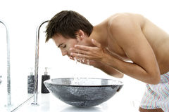 Young man splashing his face with water Stock Photos