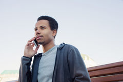 Young man in sport wear talking on mobile phone. Guy outdoors Stock Photos