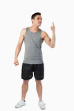 Young man in sports cloths pointing up Stock Image