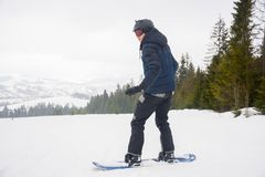 A young man in sports glasses and in the helmet is riding a snow. Board against a beautiful landscape in the mountains in Transcarpathia, Ukraine royalty free stock photography