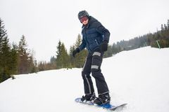 A young man in sports glasses and in the helmet is riding a snow. Board in the mountains in Transcarpathia, Ukraine stock photography