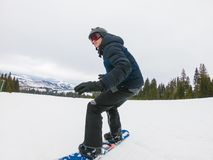 A young man in sports glasses is riding a snowboard in the mount. Ains in Transcarpathia, Ukraine stock photography