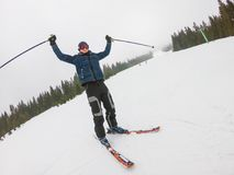 A young man in sports glasses and skiing in the mountains. A young man in sports glasses and skiing, raising his hands up in the mountains in Pylypets, in royalty free stock image