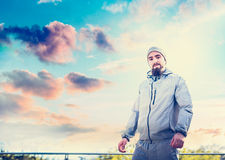 Young man in a sports suit and with a beard, standing on the terrace the background of beautiful sunset sky stock photos