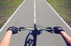 Young man-sportsman rides a mountain bike on an asphalt road Royalty Free Stock Photos