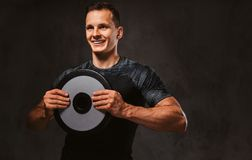 A young man in sportswear holding a barbell disk on dark background. A young happy man in sportswear holding a barbell disk on a dark background stock photography
