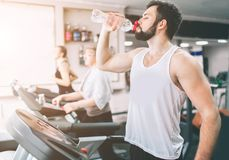 Young man in sportswear running on treadmill and drinking water at the gym. Muscular bearded athlete during workout Stock Image