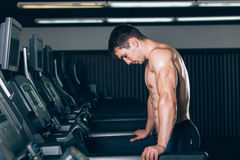 Young man in sportswear running on treadmill at gym Royalty Free Stock Photos