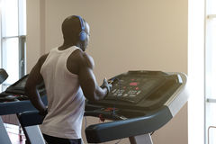 Young man in sportswear running on treadmill at gym. Young man in sportswear and headphones running on treadmill at gym Stock Image