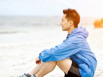 Young man sitting at the beach in sportswear Stock Photo