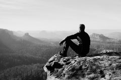 Young man in sportswear is sitting on cliff's edge and looking to misty valley bellow Stock Photos